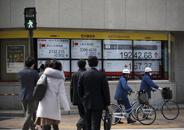Pedestrians cross a street next to an electric quotation board flashing the Nikkei key index of the Tokyo Stock Exchange (TSE) in Tokyo on March 24, 2017