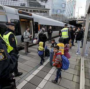 Policemen and a group of migrants stand on the platform at the Swedish end of the bridge between Sweden and Denmark in Malmo, Sweden, on November 12, 2015