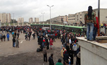 Opposition fighters and their families gather as they prepare to board a bus, ahead of their evacuation from the rebel-held Waer neighbourhood in the central city of Homs on March 18, 2017