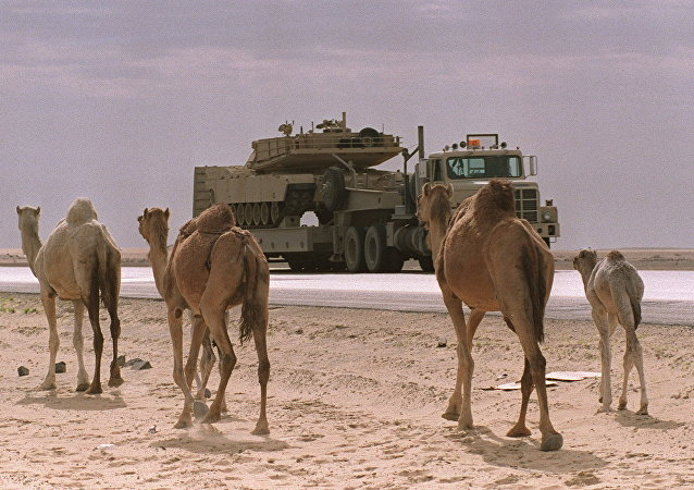 (FILES) A flat-bed truck carrying a US M-1A Abrams tank passes a group of camels in this file photo taken 03 February 1991 in the Saudi Arabian desert
