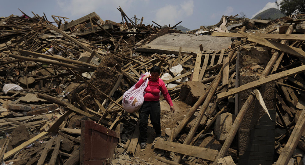 A woman carries her salvaged goods through the rubble of destroyed houses following a massive earthquake in the town of Longtoushan in Ludian County in southwest China's Yunnan Province (File)