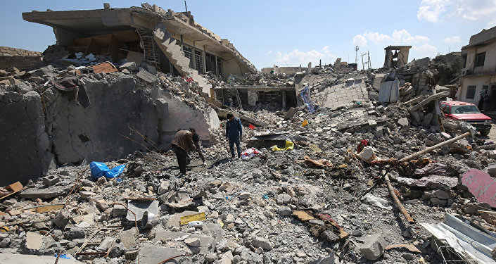 Iraqis inspect the damage in the Mosul al-Jadida area on March 26, 2017, following air strikes in which civilians have been reportedly killed during an ongoing offensive against the Islamic State (IS) group