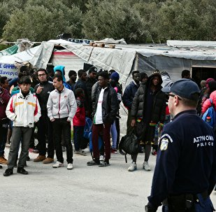 A picture taken on 16 March, 2017 shows policemen standing guard near migrants at the Moria migrant camp on the island of Lesbos, almost a year after an EU-Turkey deal