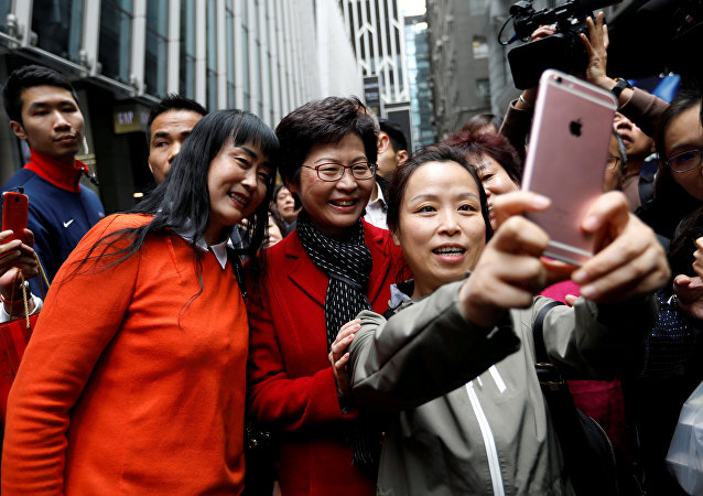 People take selfies with Carrie Lam, chief executive-elect, a day after she was elected in Hong Kong, China March 27, 2017