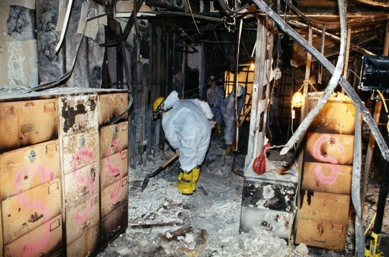 Workers scrape through the debris left behind in the ravaged west wing of the Pentagon.
