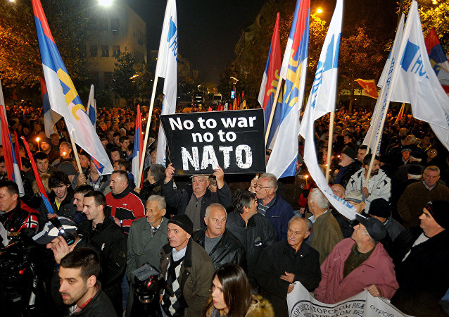 An opposition supporter holds a banner that reads No to war - no to NATO during protest in downtown Podgorica, Montenegro, Saturday, Dec. 12, 2015