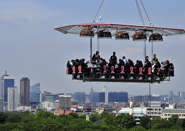 Diners take lunch suspended in the air on June 2, 2014 above the Parc du Cinquantenaire in Brussels