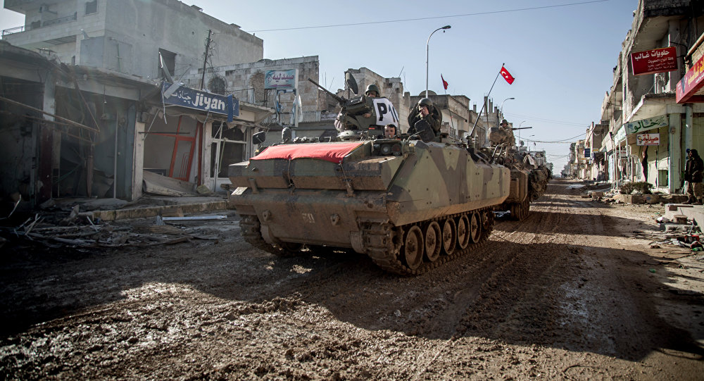 Turkish army's armored vehicles and tanks drive in Syrian town of Ayn al-Arab, also known as Kobani, as they return from the Ottoman tomb in Syria, Sunday, Feb. 22, 2015