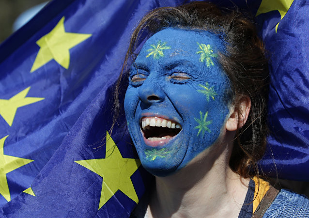 A demonstrator with her face painted in the colours of the EU flag