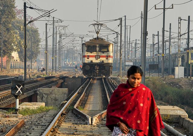 An Indian woman crosses rail tracks