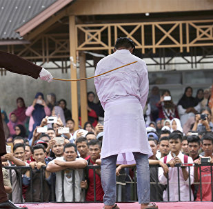 In this Monday, March 20, 2017 photo, a Sharia law official whips a man convicted of adultery with a rattan cane in Banda Aceh, Indonesia.