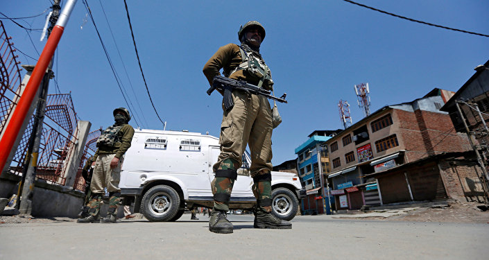 Indian policemen guard a deserted street during restrictions in downtown Srinagar April 10, 2017