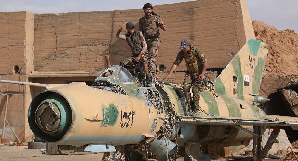 Syrian Democratic Forces (SDF) fighters gesture while posing on a damaged airplane inside Tabqa military airport after taking control of it from Islamic State fighters, west of Raqqa city, Syria April 9, 2017
