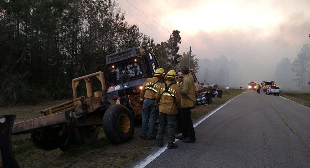 Firefighters and firefighting equipment arrive to deal with wildfire that quickly spread across acres of land, damaging many homes and forcing residents to evacuate in this image released on social media in Nassau County, Florida, U.S. on March 22, 2017