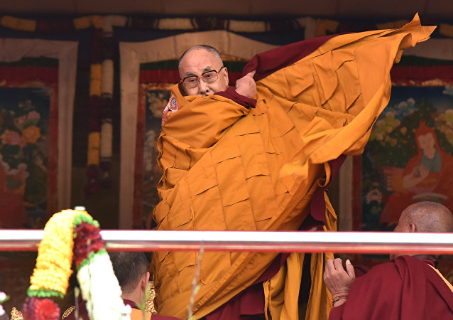 Exiled Tibetan spiritual leader the Dalai Lama adjusts his shawl as he came to deliver his religious teaching at Yiga Choezin ground at in Tawang District near India-china border in India's north-eastern state of Arunachal Pradesh state, on April 8, 2017