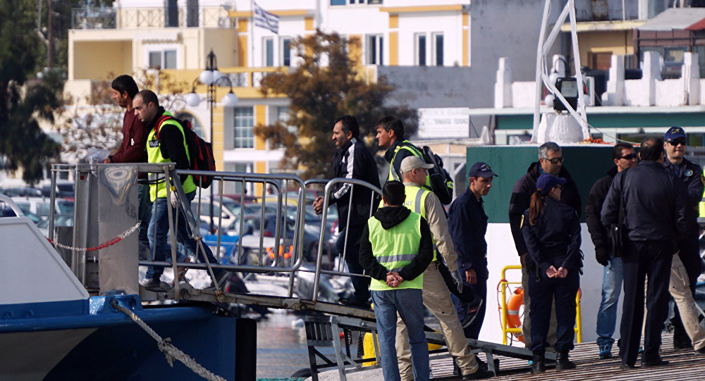 Frontex officials and Greek police escort migrants aboard a Turkish boat heading to Turkey from the port of Mytilene on the Greek island of Lesbos on October 21, 2016