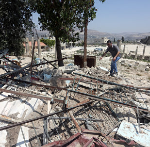 A Palestinian man walks amidst debris after Israeli authorities demolished a building in the village of Sebastia, near Nablus, in the Israeli-occupied West Bank on August 9, 2016