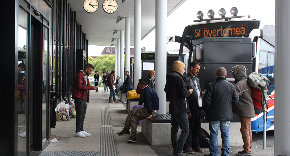 Migrants wait for a bus at the shared bus station of the northern Swedish town Haparanda and its Finnish twin town Tornio on the Swedish-Finnish border on September 21, 2015.