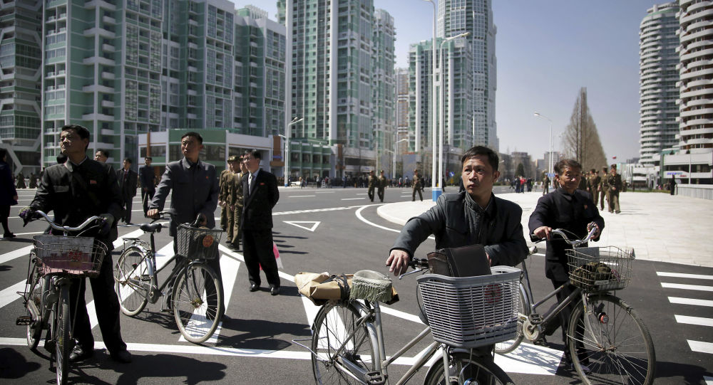 North Korean men push their bicycles along Ryomyong residential area, a collection of more than a dozen apartment buildings, on Thursday, April 13, 2017, in Pyongyang, North Korea.