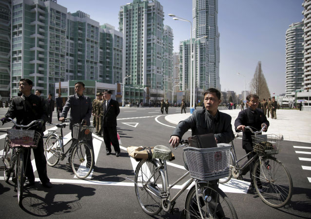 North Korean men push their bicycles along Ryomyong residential area, a collection of more than a dozen apartment buildings, on Thursday, April 13, 2017, in Pyongyang, North Korea.