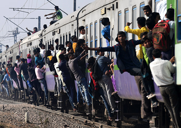 Indian passengers hang onto a train as it departs from a station on the outskirts of New Delhi on February 28, 2017