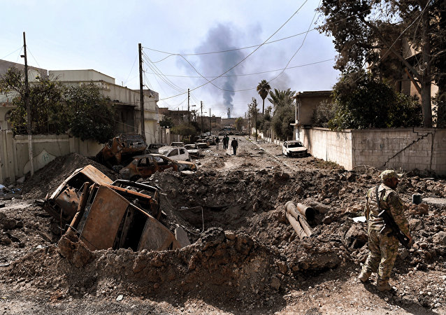 An Iraqi forces member stands next to a crater made by an airstrike in west Mosul as Iraqi troops continue battling against Daesh to further advance inside the city, on March 7, 2017