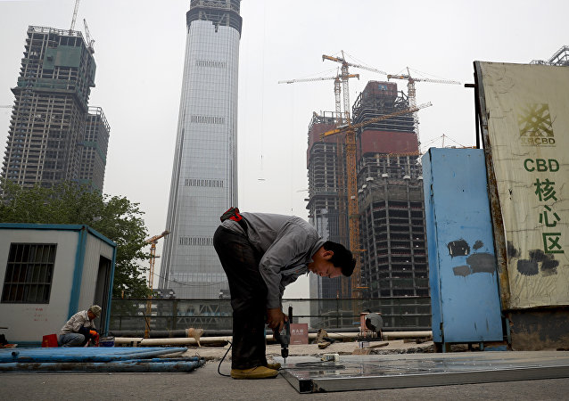 In this Sunday, April 16, 2017 photo, a worker assembles an aluminum platform outside a construction site at the Central Business District of Beijing