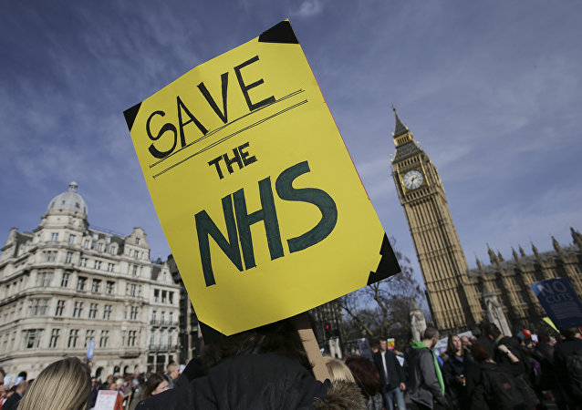 A protester holds a placard in support of the NHS in front of the Elizabeth Tower, also known as Big Ben at the Houses of Parliament during a march against private companies' involvement in the National Health Service (NHS) and social care services provision and against cuts to NHS funding in central London on March 4, 2017