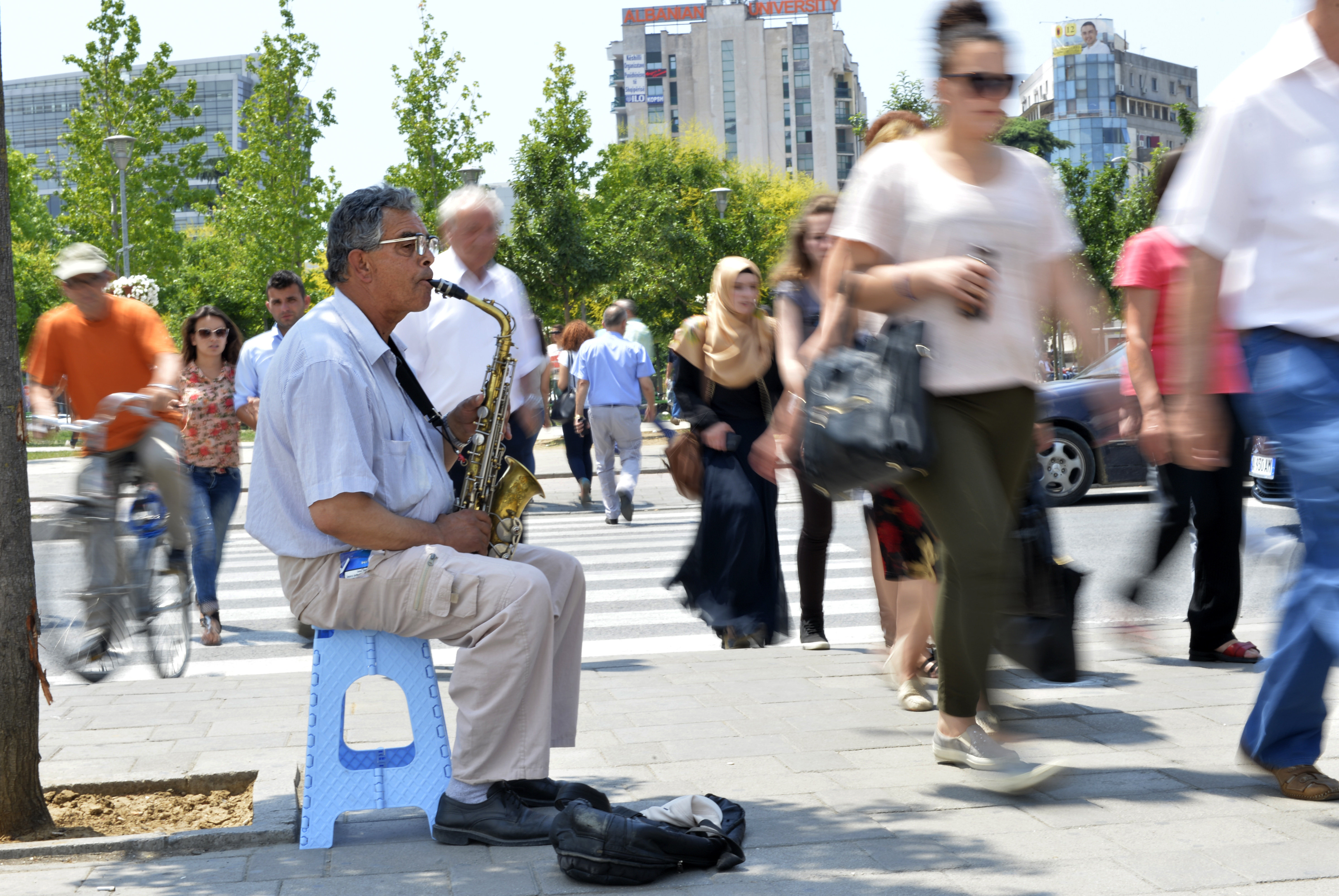 A man plays the saxophone on a street in downtown Tirana, on June 12, 2015