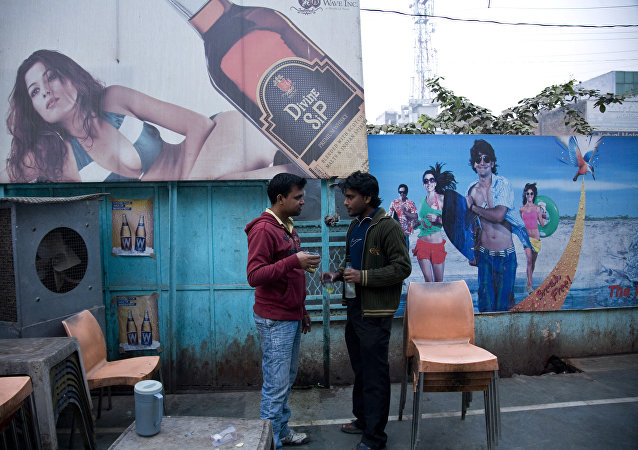 Two Indian men share a moment as they drink outside a state-sanctioned liquor shop in India.