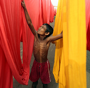In this Saturday, Dec. 22, 2012 file photo, a Bangladeshi child works at a clothes-dyeing factory in Narayanganj, outskirts of Dhaka, Bangladesh.