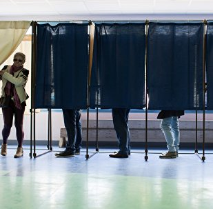 People vote at a polling station in the first round of the French presidential election