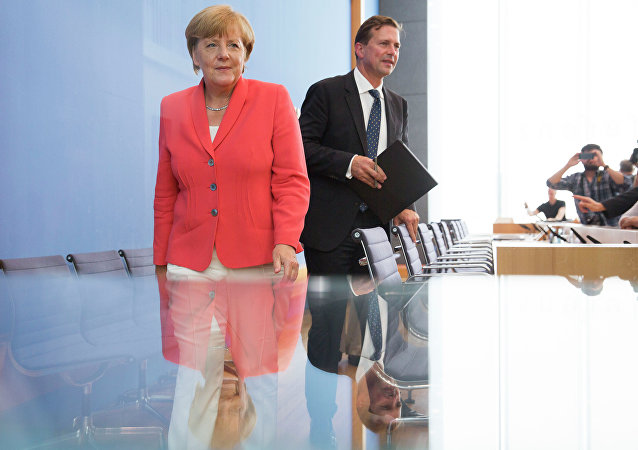 German Chancellor Angela Merkel, left, and government spokesman Steffen Seibert leave after Merkel's annual summer news conference in Berlin, Germany, Monday, Aug. 31, 2015