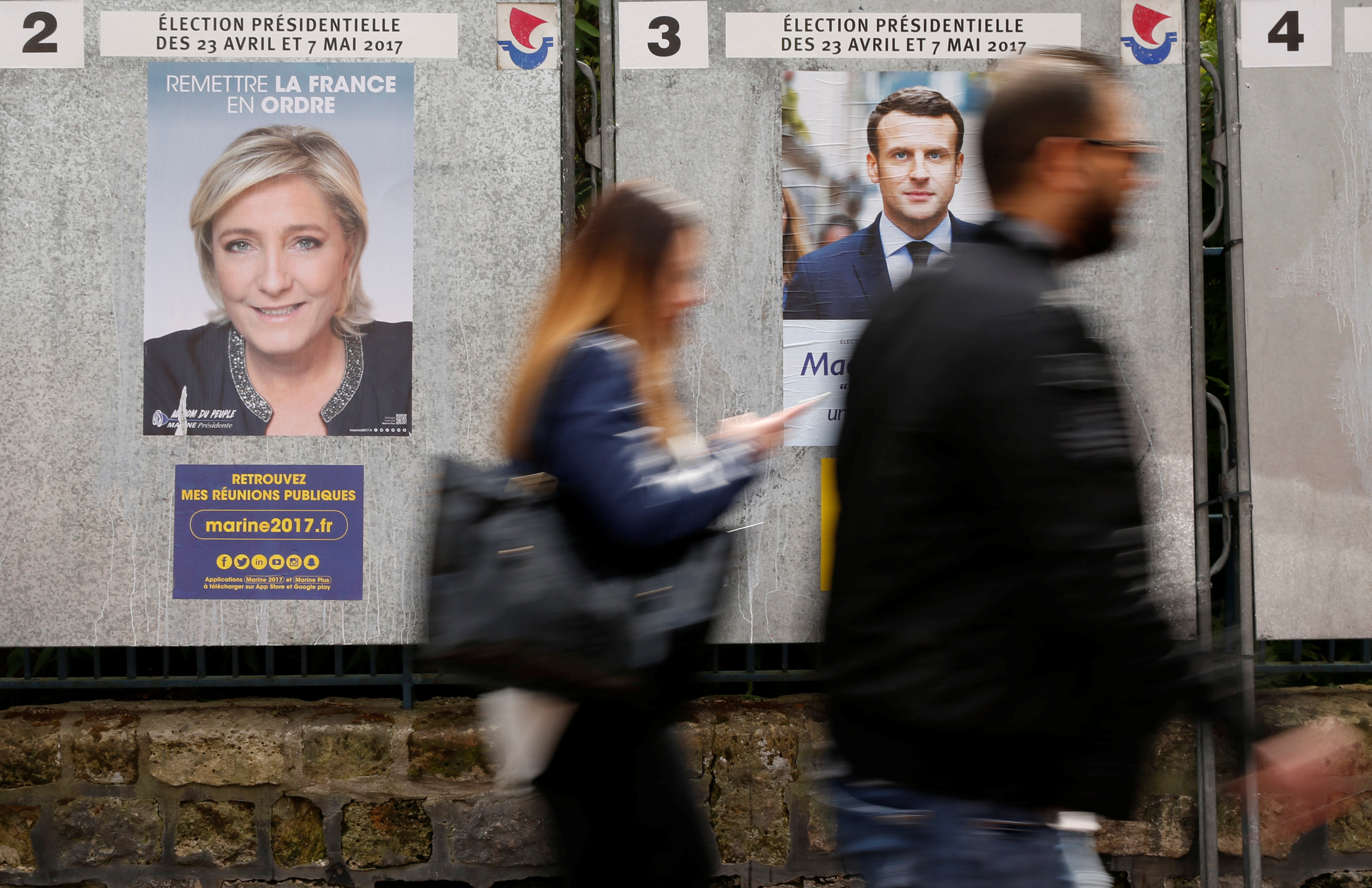 People walk past campaign posters of Marine Le Pen (L), French National Front (FN) political party leader, and Emmanuel Macron (R), head of the political movement En Marche! (Onwards!), two of the eleven candidates who run in the 2017 French presidential election in Paris, France, April 10, 2017