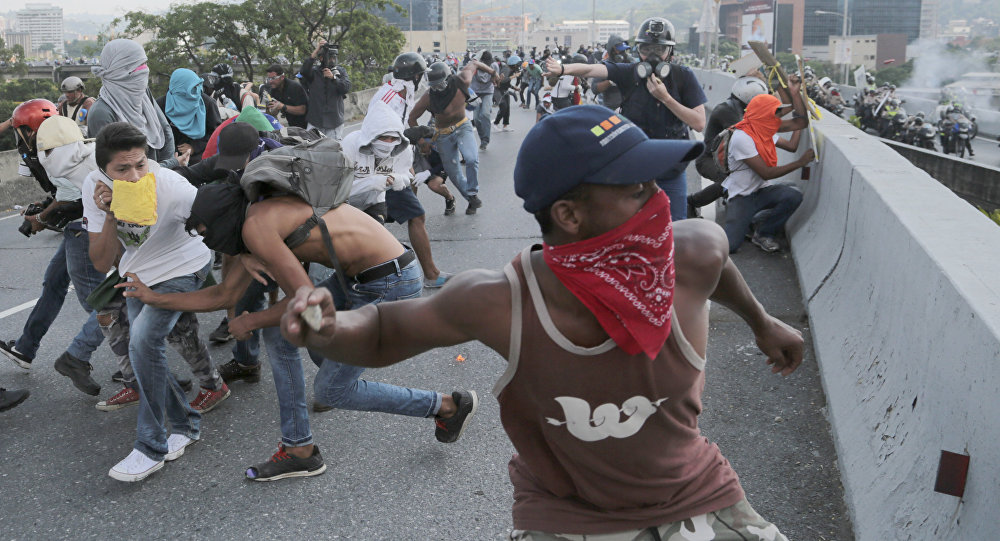 Anti-government protesters throw stones from a highway overpass at a passing police patrol in Caracas, Venezuela, Monday, April 24, 2017
