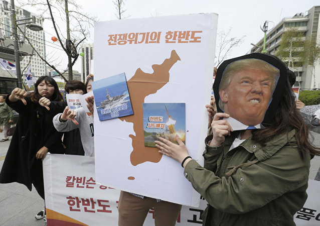 Protesters hold a cutout of U.S. President Donald Trump and images of the USS Carl Vinson aircraft carrier and U.S. missile defense system THAAD, right, on a map of Korean Peninsula during a rally against U.S. deployment of the aircraft carrier to the Korean Peninsula, near the U.S. embassy in Seoul, South Korea, Thursday, April 13, 2017