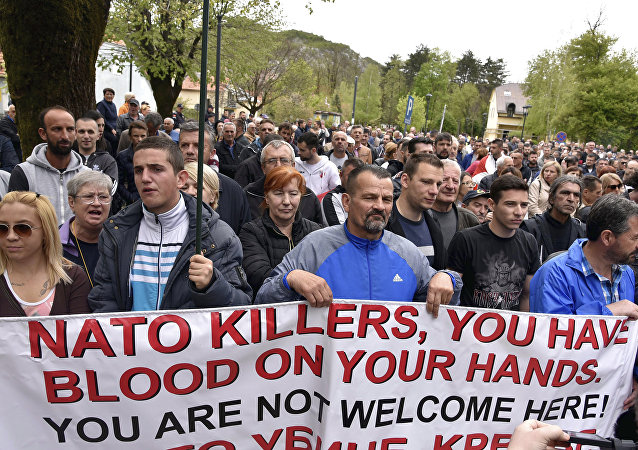 Anti-NATO demonstrators hold a banner during a protest outside the hall before the parliament session in Cetinje, Montenegro, Friday, April 28, 2017