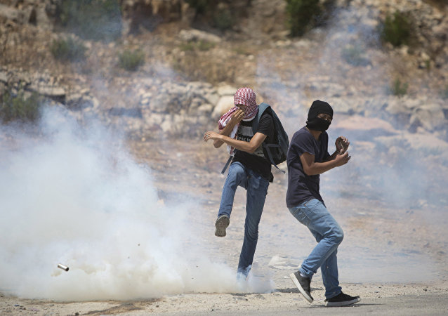 Palestinian protesters react to a tear gas canister fired by Israeli troops during a protest with solidarity hunger strike of Palestinian prisoners in the Israeli jails