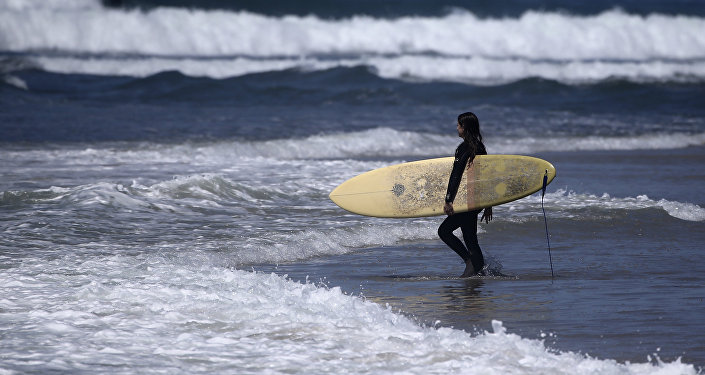 A surfer strolls into the waves at Cardiff State Beach in Encinitas, Calif.