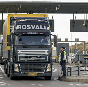 Police and customs personnel stop a freight truck at the toll booth at the Swedish end of the bridge between Sweden and Denmark in Malmo, Sweden, on November 12, 2015