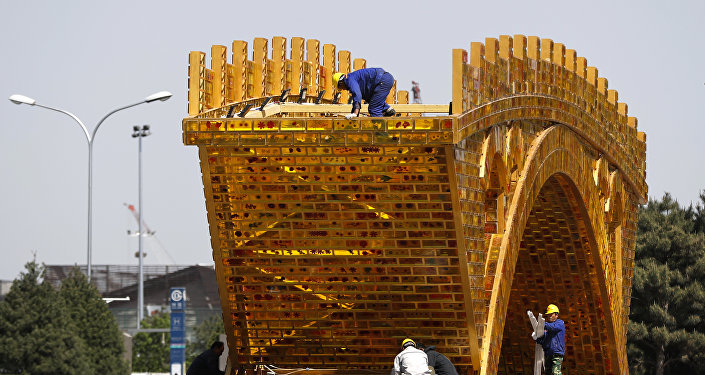 Workers install wires on a 'Golden Bridge of Silk Road' structure on a platform outside the National Convention Center, the venue which will hold the Belt and Road Forum for International Cooperation, in Beijing, April 18, 2017