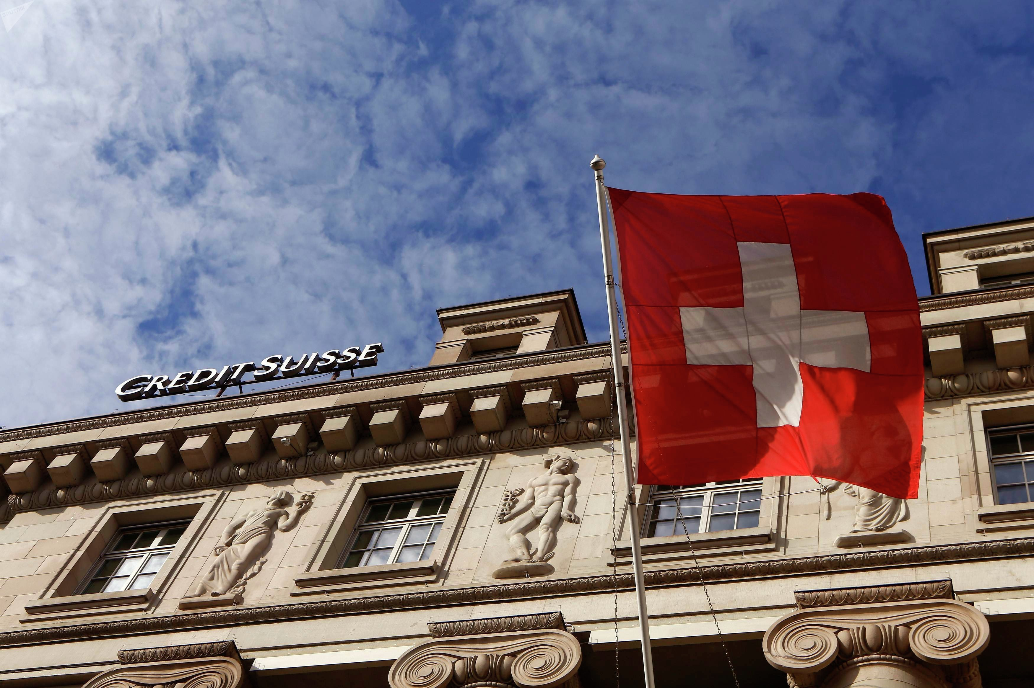 A national flag of Switzerland flies in front of a branch office of Swiss bank Credit Suisse in Luzern October 30, 2014