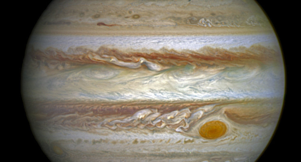 This composite image provided by NASA on Thursday, June 30, 2016 shows auroras on the planet Jupiter. This image produced by NASA using a photograph captured by the Hubble Space Telescope in spring 2014, and ultraviolet observations of the auroras in 2016.