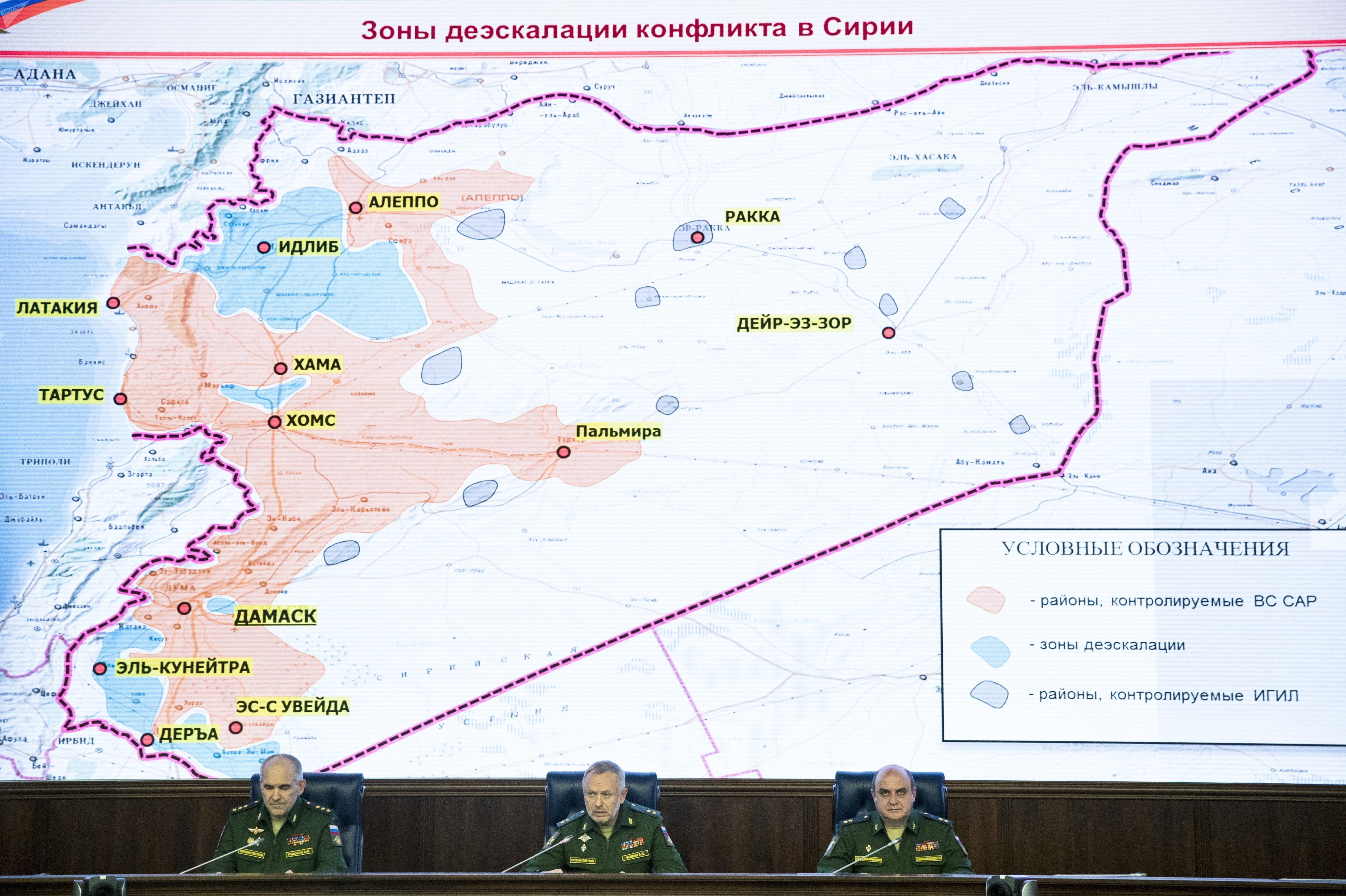 From left, Col. Gen. Sergei Rudskoi of the Russian General Staff, Deputy Defense Minister Alexander Fomin and Lt. Gen. Stanislav Gadzhimagomedov attend a briefing in the Defense Ministry in Moscow, Russia, Friday, May 5, 2017. Map displayed in the background shows regions controlled by the Syrian Army (in red), the de-escalation zones (in green), and areas controlled by Daesh (in dark blue).