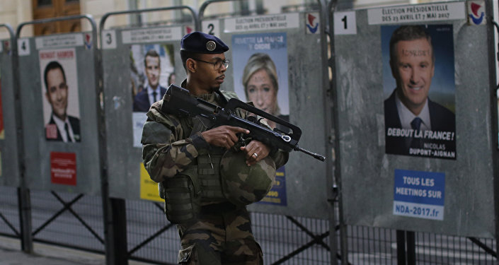 An army soldier patrols past posters showing faces of the candidates for the first-round presidential election near a polling station in Paris, Sunday, April 23, 2017