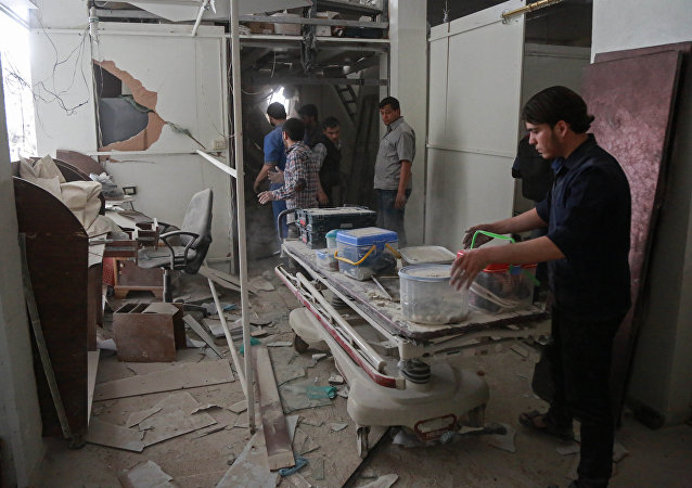 Syrians salvage medical items from a hospital following an air strike a rebel-controlled town in the eastern Ghouta region on the outskirts of the capital Damascus on May 1, 2017