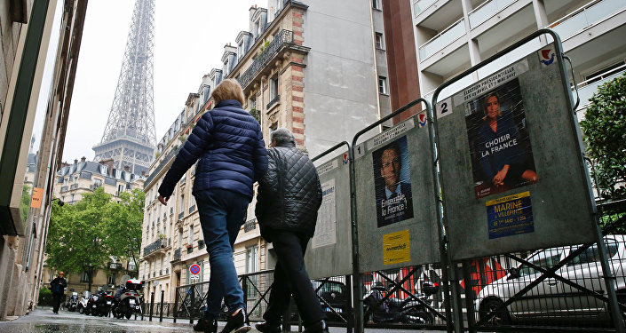 People pass election posters in Paris during the second round of 2017 French presidential election, France, May 7, 2017.