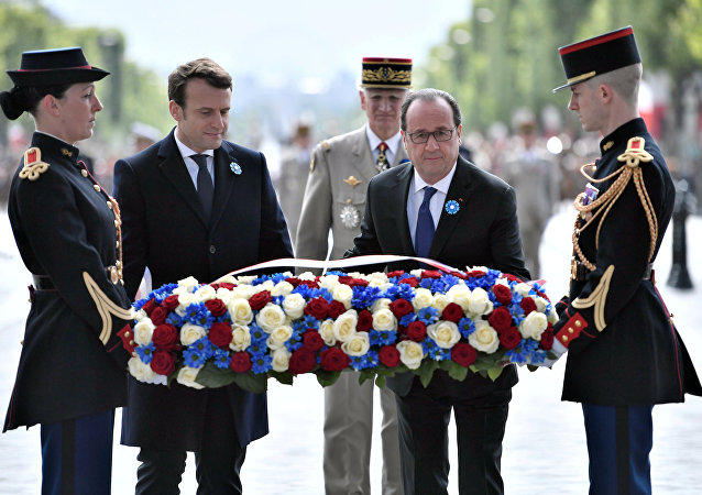 Outgoing French President Francois Hollande (R) and President-elect Emmanuel Macron attend a ceremony to mark the end of World War II at the Tomb of the Unknown Soldier at the Arc de Triomphe in Paris, France, May 8, 2017.