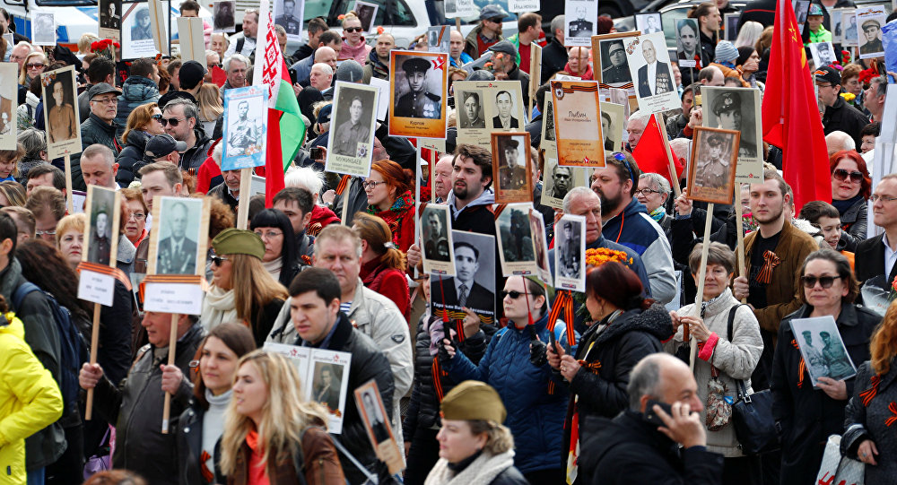 People carrying portraits of deceased relatives as they attend the Immortal Regiment march during the Victory Day celebrations at the Soviet War Memorial in Berlin, Germany