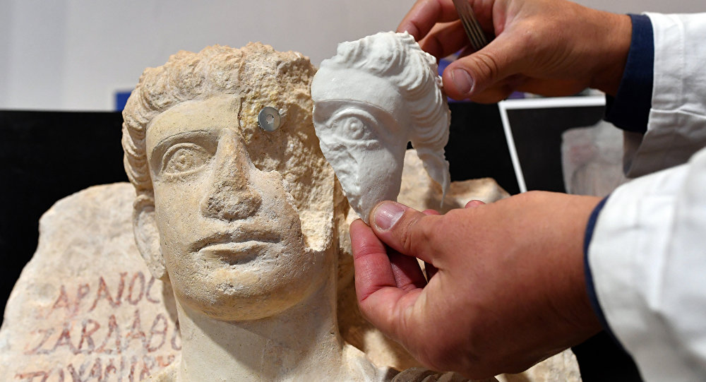 A restorer fixes a restored piece of the face of a man bust, which is one of the two funeral reliefs from Palmyra archeological site that will be restored at the Higher Institute of Conservation and Restoration (ISCR - Istituto Superiore per la Conservazione ed il Restauro) in Rome, on February 16, 2017.
